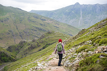 A woman walking down into Great Langdale from Crinkle Craggs with a view of Stickle Pike in the distance, Lake District National Park, Cumbria, England, United Kingdom, Europe
