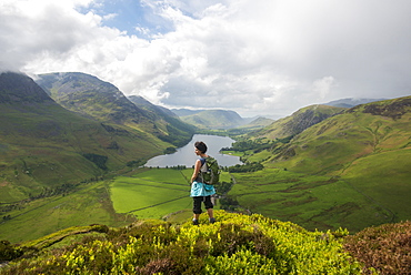 A woman looks out over Buttermere from Fleetwith Pike, Lake District National Park, Cumbria, England, United Kingdom, Europe