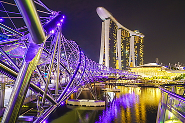 People strolling on the Helix Bridge towards the Marina Bay Sands and ArtScience Museum at night, Marina Bay, Singapore, Southeast Asia, Asia