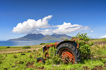 An abandoned tractor on a Cleadale Croft, with distant view of The Isle of Rhum in mid-summer, Cleadale, Island of Eigg, Small Isles, Inner Hebrides, Scotland, United Kingdom, Europe