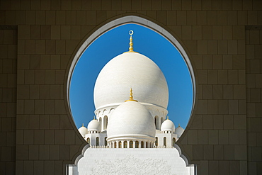 A mosque is framed by an arched passageway in Abu Dhabi, United Arab Emirates, Middle East