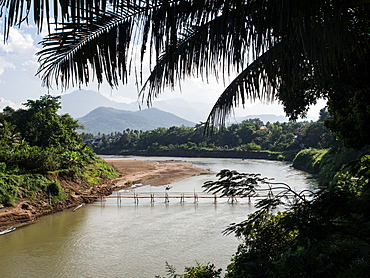 Nam Kang River with mountains, bamboo bridge, and palm trees, Luang Prabang, Laos, Indochina, Southeast Asia, Asia