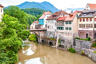 Houses lining a river, Skofja Loka village, near Ljubljana, Slovenia, Europe