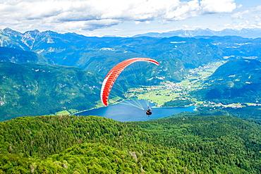 Paraglider sails over Lake Bohinj and its mountains, Slovenia, Europe
