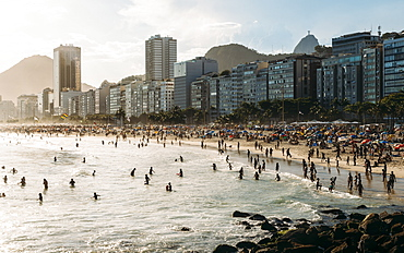 Crowded Copacabana Beach with distant view of Christ the Redeemer statue far right, Rio de Janeiro, Brazil, South America