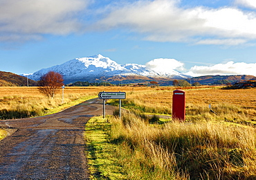Winter view of a red telephone box and road toward snow covered Beinn Resipol mountain in the moors of the Scottish Highlands, Scotland, United Kingdom, Europe - 1246-16