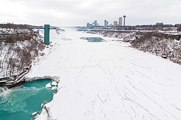 Frozen Niagara Falls in March, view from the bridge between Canada and United States of America. Ontario, Canada, North America