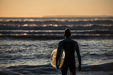 A surfer contemplating the waves at Croyde Beach in Devon, England, United Kingdom, Europe