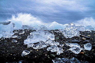 Water crashing over the ice and black sandy beach at Jokulsarlon, Iceland, Polar Regions