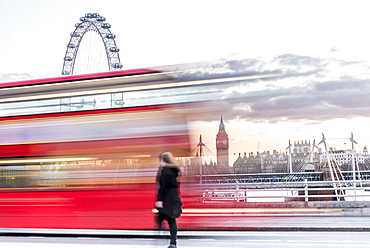 A lady crossing Waterloo Bridge with a bus passing between her, the London Eye and Big Ben, London, England, United Kingdom, Europe
