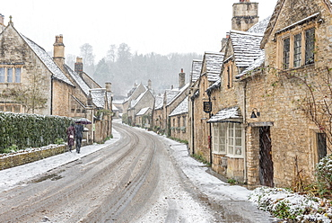 A couple walking up the hill in Castle Combe with an umbrella protecting them from the heavy snowfall, Wiltshire, England, United Kingdom, Europe