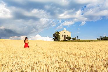 Woman in red dress admiring Notre-Dame-de-Sante chapel in a wheat field, Entrevennes, Alpes-de-Haute-Provence, Provence-Alpes-Cote d'Azur, France, Europe