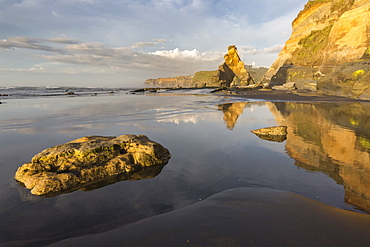 Rock formations reflected at low tide, Tongaporutu, New Plymouth district, Taranaki region, North Island, New Zealand, Pacific