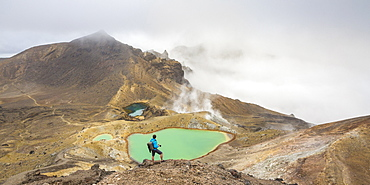 Man taking photos of Emerald Lakes, Tongariro Alpine Crossing, Tongariro National Park, UNESCO World Heritage Site, Waikato region, North Island, New Zealand, Pacific