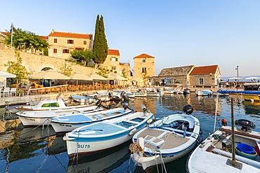 Boats at the pier of the town at sunset, Bol, Brac island, Split-Dalmatia county, Croatia, Europe