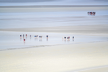 People walking on the sand during low tide, Mont-Saint-Michel, Normandy, France, Europe