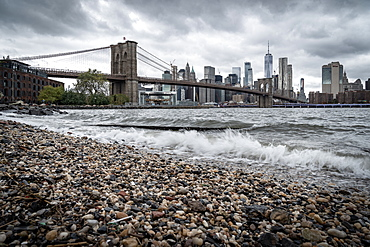 A pebble beach on the East River in Brooklyn looking towards the Brooklyn Bridge and Lower Manhattan, New York, United States of America, North America