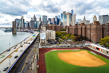 A baseball field along the FDR and East River with views towards the Brooklyn Bridge and Lower Manhattan, New York, United States of America, North America
