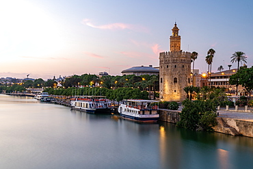 Sunset at Torre del Oro (Tower of Gold), a watchtower on the bank of the Guadalquivir River in Seville, Andalusia, Spain, Europe