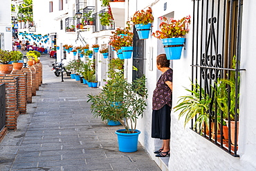 An elderly woman stands in front of a whitewashed house covered in blue plant pots in Mijas Pueblo, Andalusia, Spain, Europe