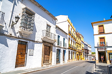 Typical white stone buildings of Andalusia, trimmed with yellow, Ronda, Andalusia, Spain, Europe