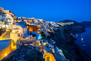The view from Oia castle along Santorini's caldera during the evening blue hour with the buildings lit, Santorini, Cyclades, Greek Islands, Greece, Europe