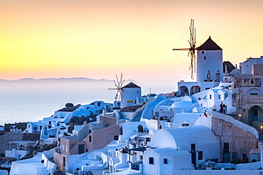 Sunset over the white stone buildings and windmills of Oia on the tip of Santorini's caldera, Santorini, Cyclades, Greek Islands, Greece, Europe