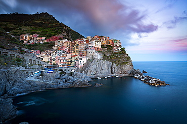 The clouds over Manarola light up with the colours of sunset during a long exposure, Manarola, Cinque Terre, UNESCO World Heritage Site, Liguria, Italy, Europe