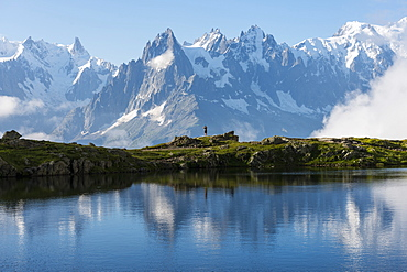 Hikers reflected in Lake Cheserys, Mont Blanc, French Alps, France, Europe
