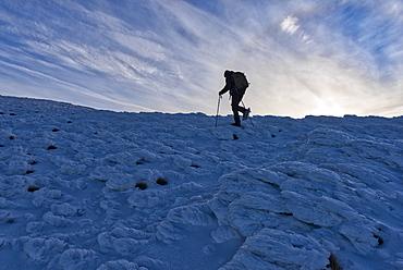 Hiker at sunrise in winter, Monte Cucco Park, Apennines, Umbria, Italy, Europe