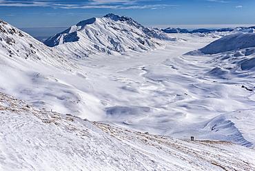 Hikers on Campo Imperatore plateau in winter, Gran Sasso e Monti della Laga, Abruzzo, Apennines, Italy, Europe