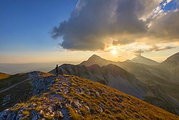 Hiker in front of mountain Portella at sunset, Gran Sasso e Monti della Laga National Park, Abruzzo, Italy, Europe
