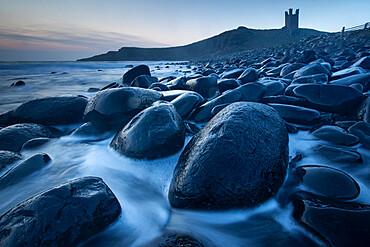 Tide swirling around black Dolerite boulders at Dunstanburgh Castle, Embleton Bay, Northumberland