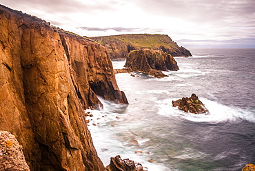 Coastal scenery with Enys Dodnan rock formation at Lands End, Cornwall, England, United Kingdom, Europe