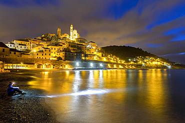 A tourist sitting on the beach observes the village at night, Cervo, Imperia province, Liguria, Italy, Europe