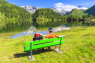 Hiker with rucksack relaxes on a bench, Lake Cavloc, Forno Valley, Maloja Pass, Engadine, Graubunden, Switzerland, Europe
