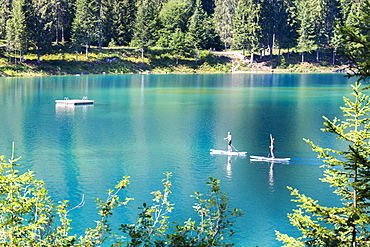 Young couple practise stand up paddling, Caumasee, Flims, District of Imboden, Canton of Grisons (Graubunden), Switzerland, Europe