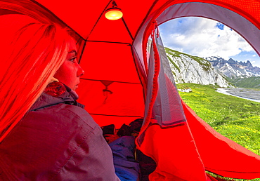 Young girls looks out of a red tent, Unterer Segnesboden, Flims, District of Imboden, Canton of Grisons (Graubunden), Switzerland, Europe