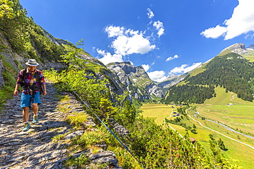 A hiker walks along the path called Scala Mola, Val Bargis valley, Flims, District of Imboden, Canton of Grisons (Graubunden), Switzerland, Europe