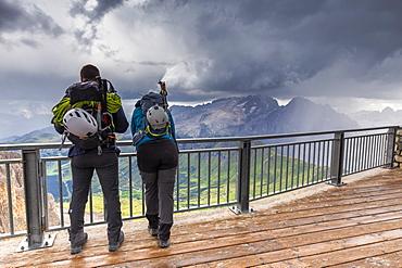 Two mountain climbers watch the storm above Marmolada, Pordoi Pass, Fassa Valley, Trentino, Dolomites, Italy, Europe