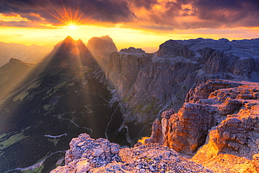 Sun rays filter between stormy clouds during sunset with Sassolungo group in the foreground, Fassa Valley, Trentino, Dolomites, Italy, Europe