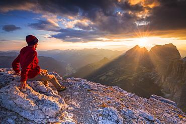 Hiker looks at sunset from Piz Pordoi, Fassa Valley, Trentino, Dolomites, Italy, Europe