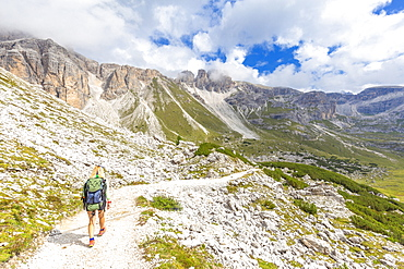A hiker walks the path for Pian di Cengia Refug, Dolomites of Sesto (Sexten), Province of Belluno, Veneto, Italy, Europe
