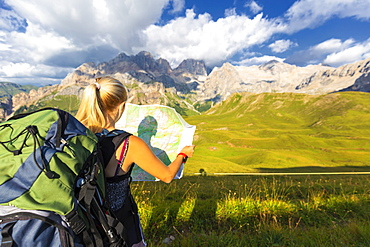 Hiker reading map with Marmolada in the background, San Nicolo Pass, Fassa Valley, Trentino, Dolomites, Italy, Europe