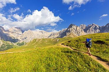 Hiker walking on a path near San Nicolo Pass, Fassa Valley, Trentino, Dolomites, Italy, Europe