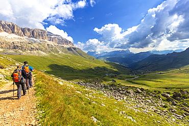 Hikers walk on a path near Pordoi Pass, Fassa Valley, Trentino, Dolomites, Italy, Europe