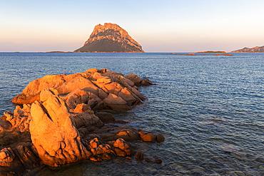 Sun illuminates rocks with Tavolara Island in the background at sunset, Loiri Porto San Paolo, Olbia Tempio province, Sardinia, Italy, Mediterranean, Europe