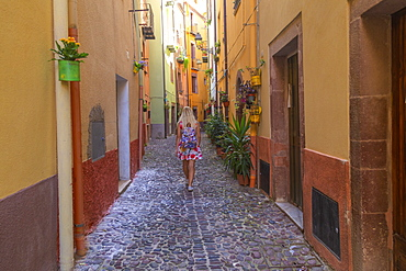 A girl walks in a street of Bosa, Oristano province, Sardinia, Italy, Mediterranean, Europe