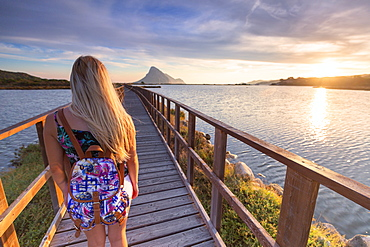 A girl looks at sunrise from a pedestrian walkway, Porto Taverna, Loiri Porto San Paolo, Olbia Tempio province, Sardinia, Italy, Mediterranean, Europe