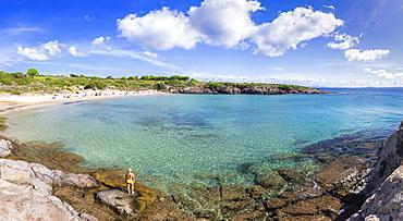 Girl in swimsuit looks at the beach, La Bobba Beach, San Pietro Island, Sud Sardegna province, Sardinia, Italy, Mediterranean, Europe